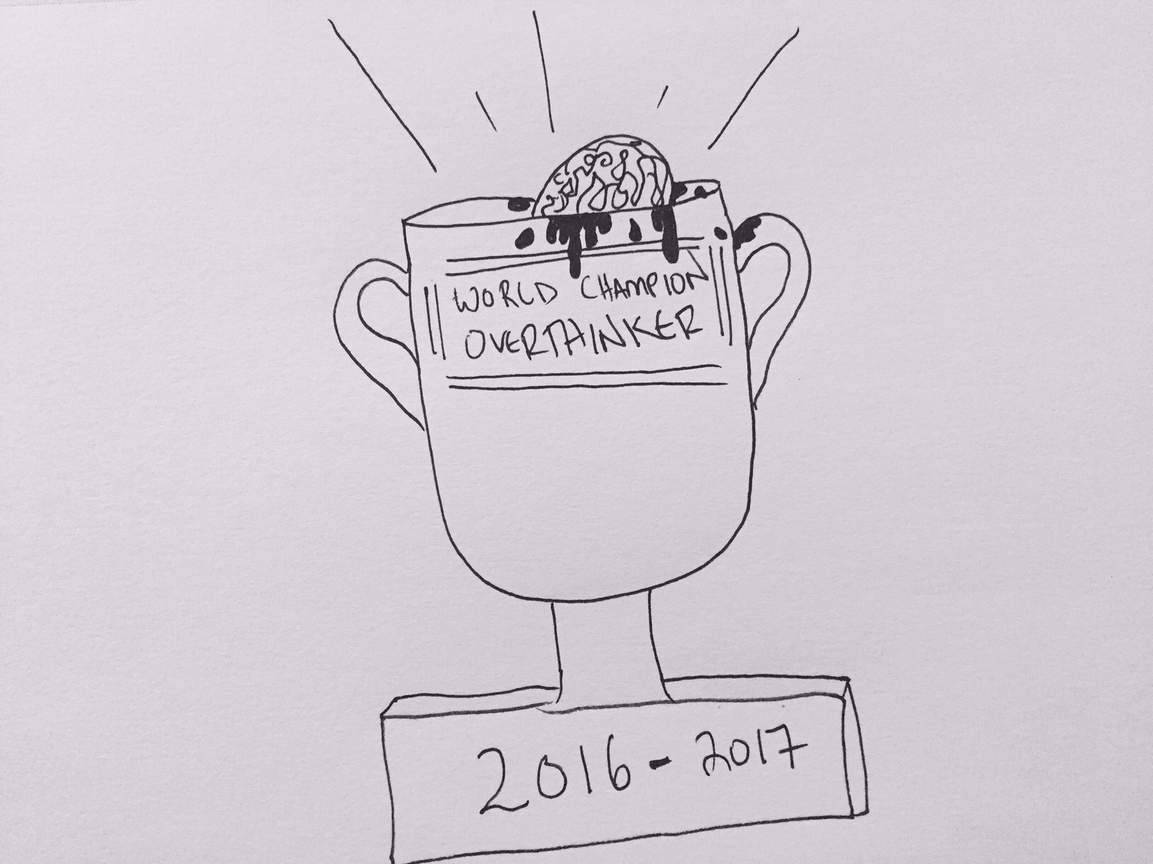 "A trophy featuring the inscription ""World Champion Overthinker 2016-2017"" shines brightly. There is a brain surrounded by specks of blood in the trophy."