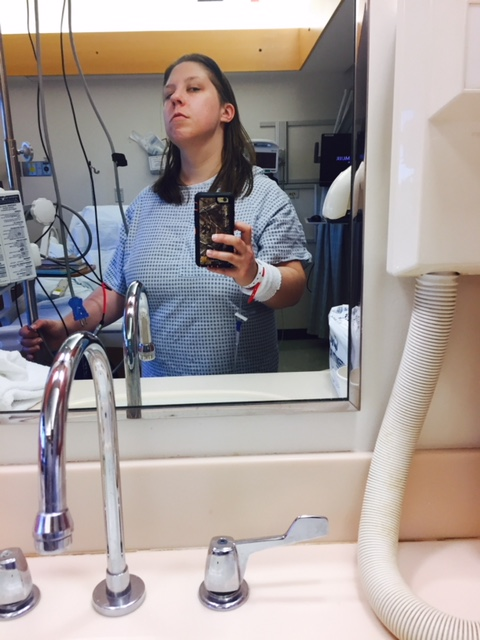 Image of a white woman in a hospital setting. She is pointing her phone at a mirror and scowling.